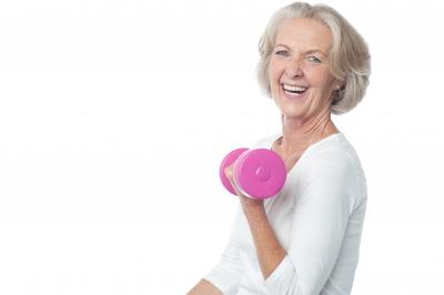 Joyous woman lifting dumbbles